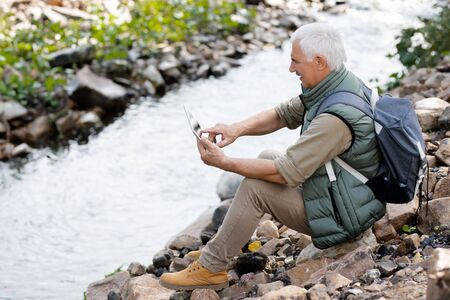 Aged man in activewear pointing at touchpad display while sitting on river bank