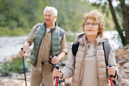 Pretty mature female hiker and her husband moving down river bank