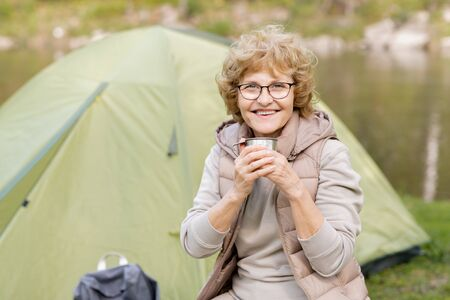 Happy mature female with hot drink looking at you while enjoying rest by tent Stock Photo