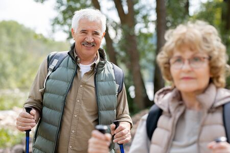 One of mature hikers looking at you while enjoying weekend trip with his wife