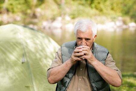 Senior hiker with grey hair drinking hot tea from tourist mug while having rest