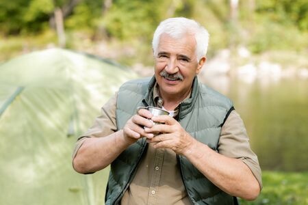 Happy senior active man with hot drink looking at you while enjoying his trip Stock Photo