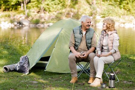 Cheerful hikers in activewear enjoying rest by tent in natural environment