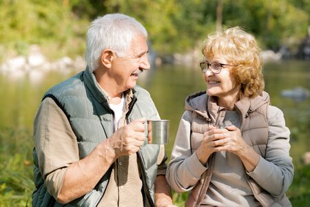 Happy mature active hikers with hot tea enjoying rest on sunny day Stock Photo