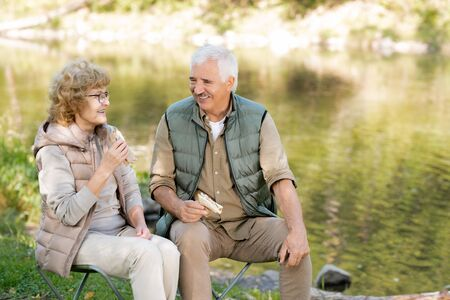 Two happy mature hikers with sandwiches discussing funny moments of their trip Stock Photo - 129800140