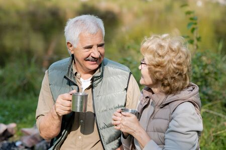 Happy mature man and his wife with tourist mugs having tea and talk Stock Photo - 129800146