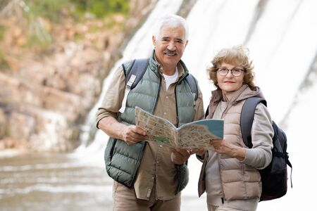 Happy senior couple with backpacks and map standing in front of camera