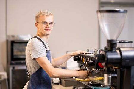 Successful barista in uniform using coffee machine while standing by workplace