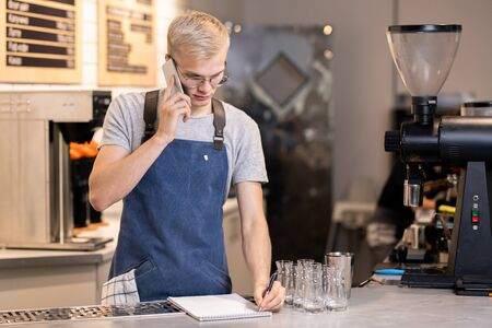 Young serious waiter or barista writing down order of client on the phone Stock fotó
