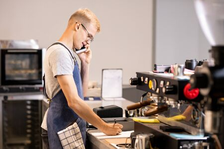 Young waiter or worker of cafeteria writing down orders of clients in notepad