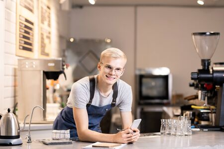 Young cheerful barista in workwear looking at you while bending over table