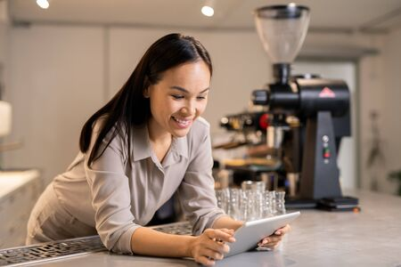 Busy young manager with touchpad leaning on table while surfing in the net