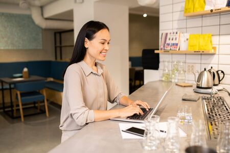 Young female barista or waitress of restaurant networking in front of laptop