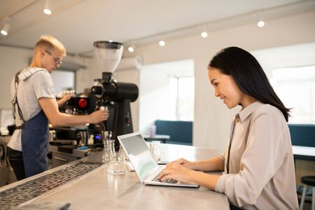Young client of cafeteria surfing in the net with barista on background