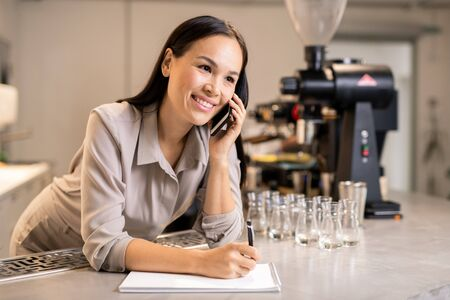 Young smiling barista in workwear making notes in notepad while phoning clients 写真素材