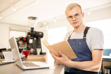 Young serious barista in workwear reading literature about restaurant business Banque d'images - 130061746