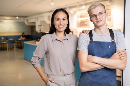 Happy young colleagues in workwear standing inside modern cafe or restaurant