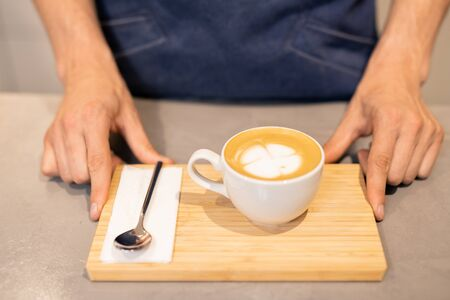 Porcelain cup of cappuccino and small spoon with paper napkin on wooden tray