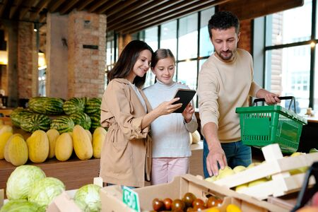 Happy mother and daughter reading points of shopping list in supermarket Stock Photo