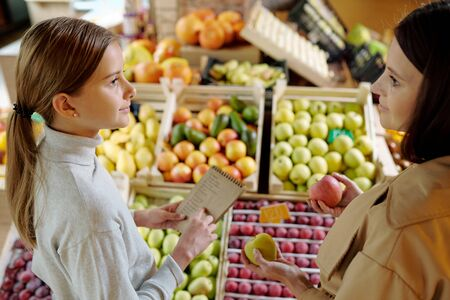 Young brunette woman with apples looking at her daughter with shopping list Stock Photo