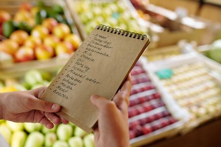 Notepad with list of products to buy in supermarket held by youthful girl