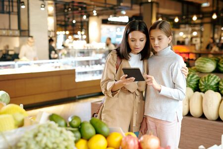 Affectionate young woman and her daughter reading shopping list in notepad Stock Photo