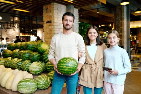 Young casual family of three buying ripe watermelon in modern supermarket