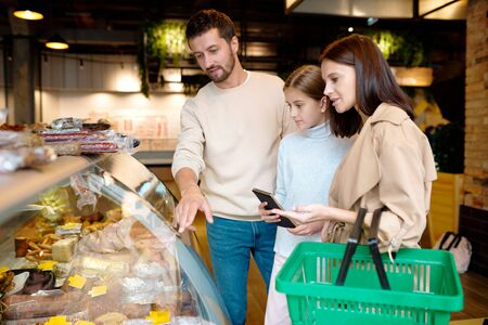 Contemporary family of three choosing meat products in supermarket