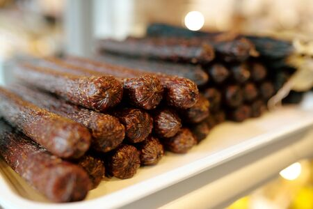 Stack of tasty and spicy fresh sausages in display with meat products