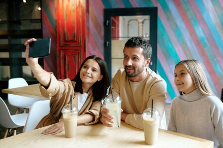 Young cheerful family of three resting by table in cafe after shopping