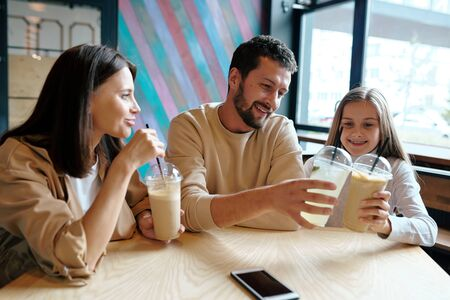 Young man and his daughter clinking with plastic glasses of milk cocktail Stock Photo