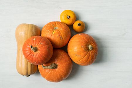 Pile of large orange pumpkins and two yellow small ones over white background Imagens