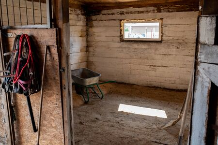 Empty stable for racehorses with small window, worktools and cart