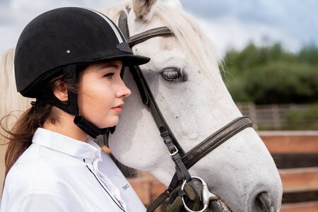 Young calm female in white shirt and equestrian helmet standing by racehorse