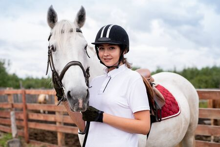 Young smiling woman in equestrian outfit standing close to white racehorse