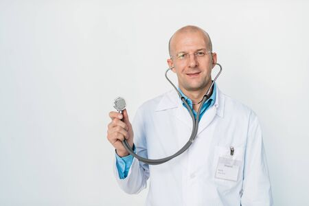 Smiling bald doctor with stethoscope looking at you before examination
