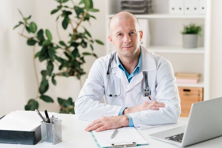 Young confident clinician in whitecoat sitting by desk in front of laptop