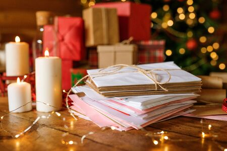 Stack of letters for Santa, three burning candles and group of packed gifts Stock Photo