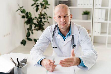 Zuversichtlicher Arzt mit Stethoskop und Stift, der Sie medizinisch berät