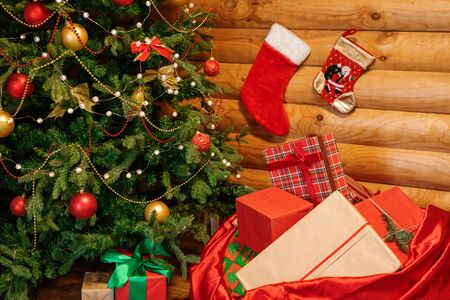 Open red sack full of Christmas presents by decorated firtree and wooden wall with two socks for gifts
