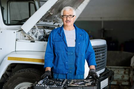 Mature master of machine repair service in blue workwear standing by lorry