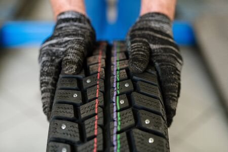 New tyre for car or lorry held by worker of contemporary machine repair service Stock Photo