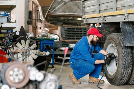 Young technical engineer of car repair service drilling wheel of machine