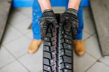 Gloved hands of contemporary technical service worker moving new tyre forwards