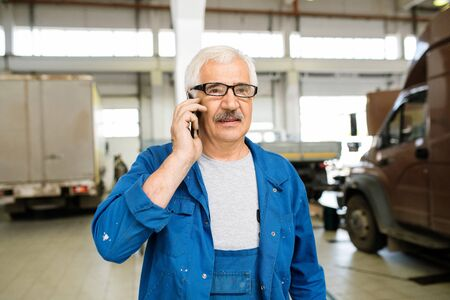 Senior technician in workwear and eyeglasses consulting client on mobile phone