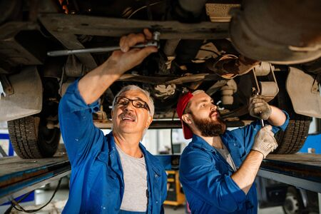 Young and mature technicians of car repair service fixing details of car motor