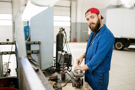 Young bearded repairman using wrench or other handtool to fix parts of engine Standard-Bild