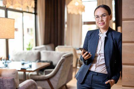 Young successful businesswoman in formalwear scrolling in mobile phone Reklamní fotografie