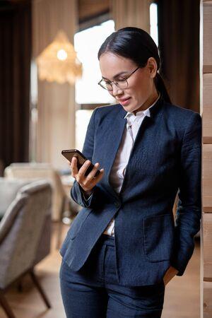 Happy Asian female in elegant suit reading message or scrolling in smartphone Reklamní fotografie