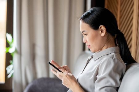 Pretty Asian woman with dark long hair scrolling or texting in smartphone